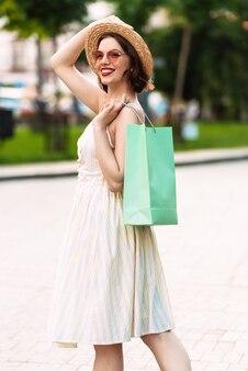 Вертикальное изображение улыбающейся женщины в платье, соломенной шляпе и солнцезащитных очках, позирующей с пакетами на открытом воздухе