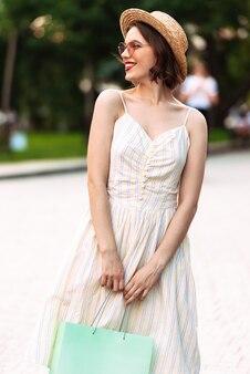 Вертикальное изображение улыбающейся женщины в платье, соломенной шляпе и солнцезащитных очках, позирующей с пакетами, глядя в сторону на открытом воздухе
