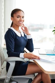 オフィスの窓の近くの肘掛け椅子に座ってカメラを見ているドレスを着た若いアフリカのビジネス女性の垂直方向の画像