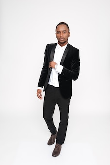 Вертикальное изображение молодого африканского человека в костюме. вся длина. изолированный белый фон
