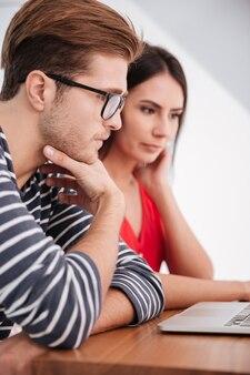 Вертикальное изображение молодой концентрированной пары, сидящей за столом с ноутбуком в офисе. обрезанное изображение
