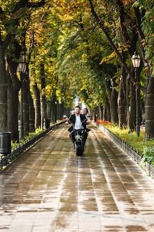 モダンなバイクに乗るエレガントなカップルの垂直方向の画像