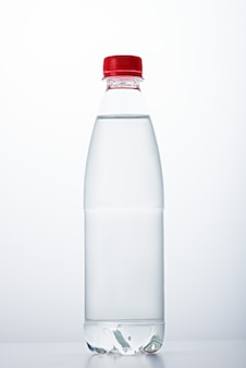 Vertical image of one plastic bottle with red lid filled with water on white background