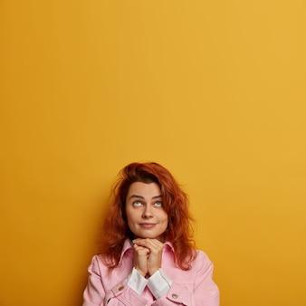 L'immagine verticale di una donna adorabile e pensierosa guarda, si spera, sopra, tiene le mani sotto il mento e prega per un buon benessere, ha i capelli rossi