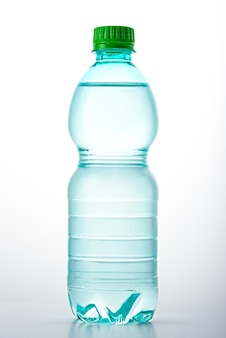 Vertical image of plastic clean bottle with green lid filled with water on white background