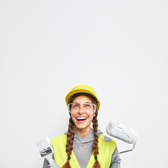Vertical image of positive female construction worker holds equipment for painting walls dressed in work clothes focused above with cheerful expression isolated over white wall with empty space