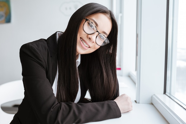 Vertical image of pretty asian business woman near the window