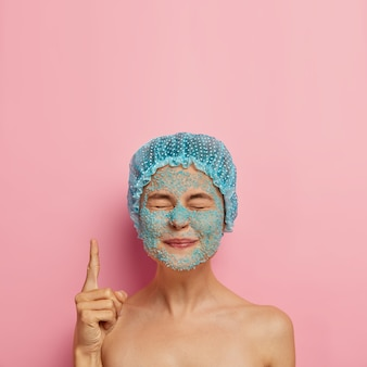 Vertical image of satisfied beauty girl has blue sea salt scrub on face, closes eyes and points index finger upwards, wears bathcap, spends weekend in spa salon has problematic dry skin, beauty regime