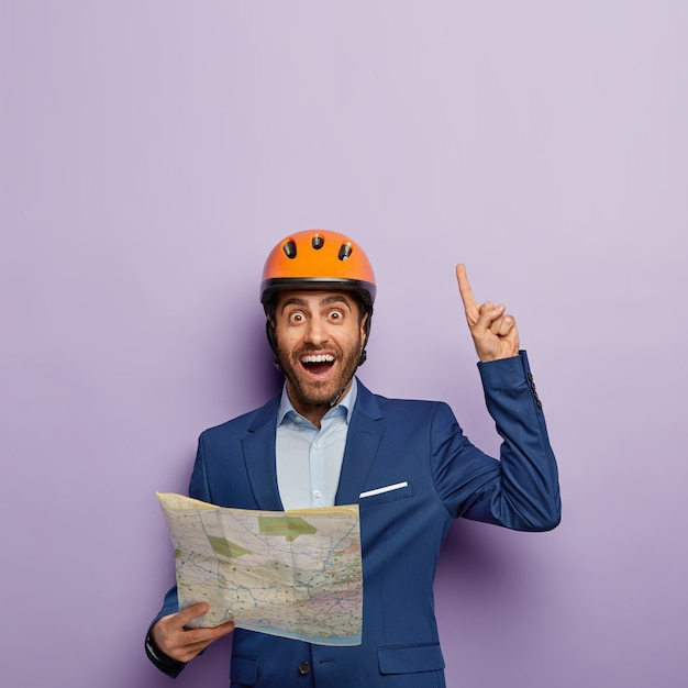Vertical image of satisfied male architect with blueprint, points above with index finger, has happy look, demonstrates something upwards, has idea in mind, wears protective hardhat, elegant suit
