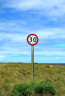 Vertical image of speed limit signpost on the roadside of easter island, chile, south america