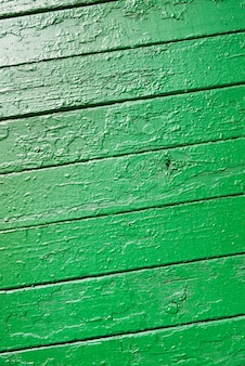 Vertical image of the texture of wooden boards, painted with green paint, locally peeled.