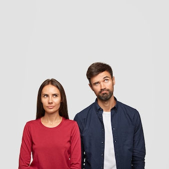 Vertical image of thoughtful couple have confused facial expression