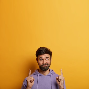 Vertical image of unimpressed bearded man purses lips, points above, shows copy space area, looks unbothered and careless, isolated over yellow wall, demonstrates place for your promotion