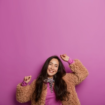 Vertical image of upbeat happy korean woman with long dark hair, tilts head and keeps arms raised, has dreamy expressions