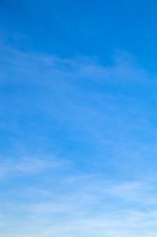 Вертикальное изображение белых облаков в голубом небе утром