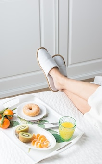 Vertical image of a woman's legs with hotel slippers and a bathrobe on top of a bed with a white quilt next to a breakfast tray with tangerine kiwi donut and orange juice