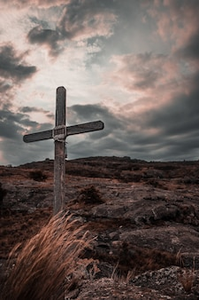 Vertical image of a wooden cross on the rocky mountains of mallin in cordoba, argentina