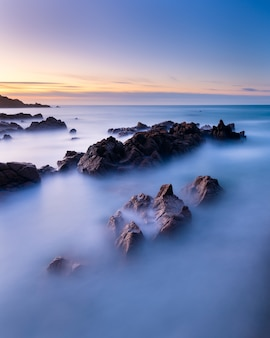Colpo verticale di lunga esposizione del paesaggio marino a guernsey durante il tramonto
