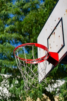 Vertical low angle shot of a basketball hoop with a blurred