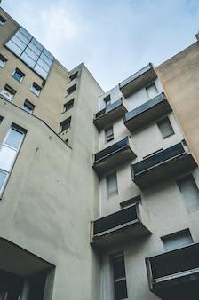 Colpo verticale di angolo basso di una costruzione architettonica astratta marrone con i balconi e le finestre