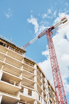 Vertical low angle shot of construction crane building residential house against blue sky, copy space