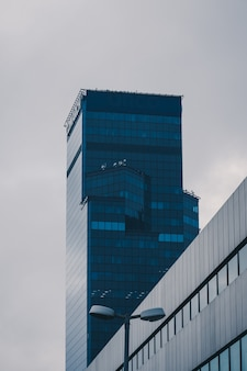 Colpo verticale di angolo basso di un grattacielo in una facciata di vetro sotto il chiaro cielo