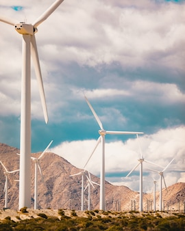 Inquadratura dal basso verticale di molti mulini a vento in un campo circondato da alte montagne rocciose