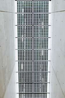 Vertical low angle shot of the metal ceiling in a white concrete hallway