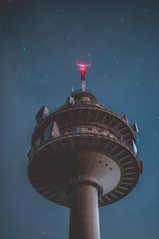 아름다운 별 밤에 회색 높이 타워의 수직 낮은 각도 샷