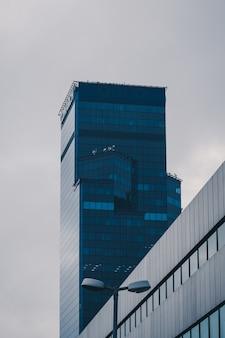 澄んだ空の下でガラスのファサードの高層ビルの垂直ローアングルショット
