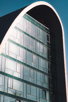 유리 창문이있는 고층 빌딩의 수직 낮은 각도 샷