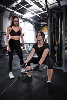 Вертикальный снимок под низким углом профессиональной спортсменки, обучающей своего клиента сидению на корточках в кроссовере