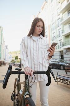그녀의 자전거와 함께 도시를 걷는 스마트 폰을 사용하는 여성의 수직 낮은 각도 샷