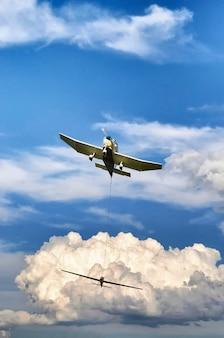 青い曇り空の下で飛行機の垂直ローアングルショット Premium写真