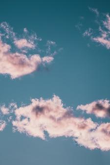 青い空に浮かぶ壮大なふわふわ雲の縦ローアングルショット