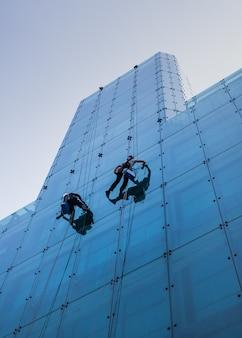 Вертикальный снимок двух человек, поднимающихся на высокое стеклянное здание в дневное время под низким углом.
