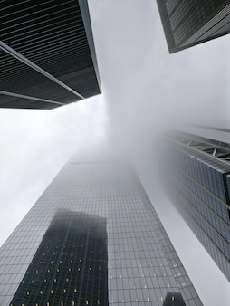 Vertical low angle shot of a tower block enveloped in fog