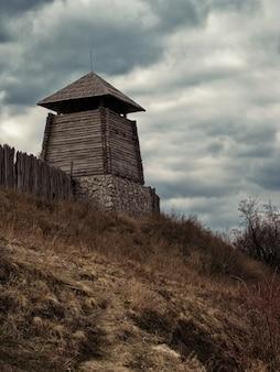 Inquadratura dal basso verticale di una costruzione in legno vicino a un recinto sotto un cielo nuvoloso
