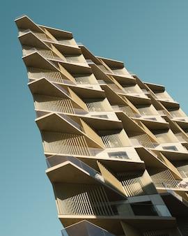 Вертикальный низкий угол обзора бежевого металлического здания под голубым небом