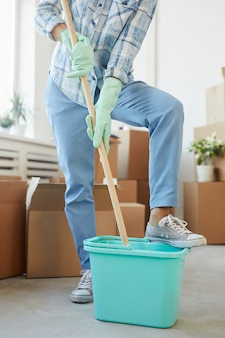 Vertical low section portrait of cheerful young woman cleaning new house or apartment while moving in