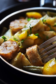 Vertical macro photo of fried potatoes with sausages, beans and pepper