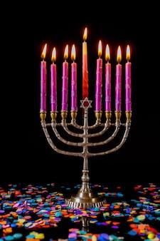 Вертикальная менора с розовыми зажженными свечами и конфетти на еврейский праздник ханука.