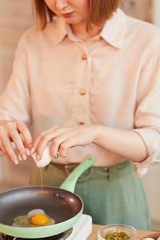 부엌 인테리어에서 건강한 아침 식사를 요리하는 동안 계란을 깨는 현대 젊은 여자의 세로 중간 섹션 초상화