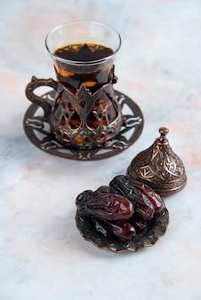 灰色の表面に乾燥したナツメヤシと新鮮なお茶の垂直