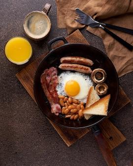 Вертикальный традиционный жареный на сковороде вкусный жирный деревенский английский завтрак на деревянном фоне
