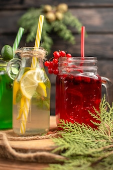 Verticale di succhi di frutta organici in bottiglie serviti con tubi su un tagliere di legno su un tavolo marrone