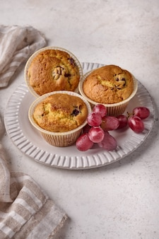 明るい背景にナプキンとプレートにさくらんぼとブドウの垂直方向のカップケーキ