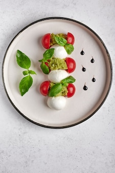 Vertical orientation delicious italian caprese salad with ripe tomatoes, fresh garden basil and mozzarella cheese