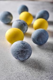 垂直方向の自家製イースター色の黄色と灰色の大理石の卵