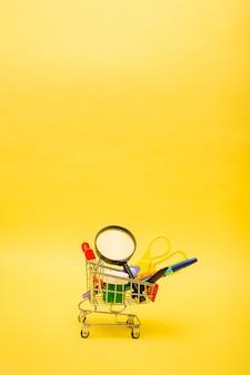 Вертикальная ориентация канцелярские товары в металлической тележке на желтом изолированном фоне с копией пространства